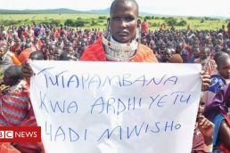 A Maasai woman holds a sign that reads in Swahili: We will fight for our land until the end.